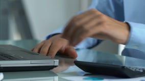 Accountant die aan laptop werken, en financiële gegevens over firma berekenen melden stock footage
