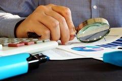 Accountant die financieel verslag met vergrootglas controleren Boekhouding stock afbeelding