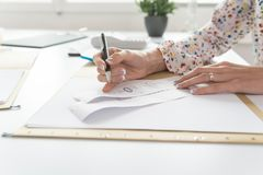 Accountant or financial adviser checking and comparing receipts. While making a final report, working at her desk with calculator alongside Stock Photo