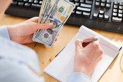 Accountant Holding Cash and Taking Notes Stock Photos
