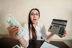 Accountant holding dollars and calculator in hands Stock Image