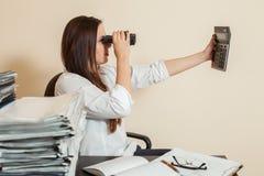 Accountant looks through binoculars on calculator Stock Image