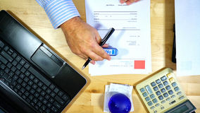 Accountant paying invoices. Accountants desk paying invoices, overhead, using dummy invoices with fake names and addresses Royalty Free Stock Photography