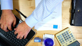 Accountant paying invoices. Accountants desk paying invoices, overhead, using dummy invoices with fake names and addresses Royalty Free Stock Photo