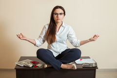 Accountant sitting in yoga pose on the table Royalty Free Stock Images