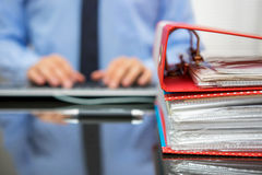 Accountant with stack of invoices is inserting data into compute Royalty Free Stock Photography