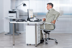 Accountant Suffering From Back Pain At Desk. Side view of accountant suffering from back pain at desk in office Royalty Free Stock Photography