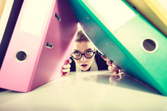 Accountant terrified of pils of binders. Royalty Free Stock Image