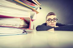 Accountant terrified of pils of binders. A lot of work and overwork concept. Terrified young businesswoman secretary with huge stack of binders. Scared Stock Photography