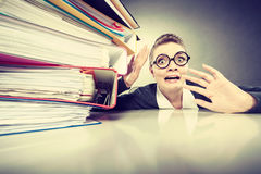 Accountant terrified of pils of binders. A lot of work and overwork concept. Terrified young businesswoman secretary with huge stack of binders. Scared Stock Photo