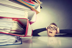 Accountant terrified of pils of binders. A lot of work and overwork concept. Terrified young businesswoman secretary with huge stack of binders. Scared Stock Photos