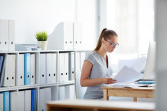 Accountant at work. Young accountant looking through papers at workplace stock images