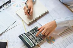 Accountant working on desk to using calculator with pen on book. Concept finance stock photo