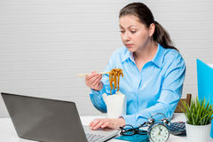Accountant working on laptop and eating noodles Stock Photography