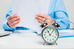 Accountant working in the office, alarm clock. In focus close-up Stock Photos