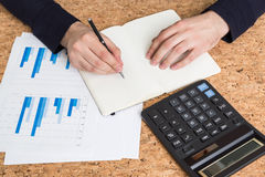 Accountant writing in notepad. Top view of male hands writing in notepad on cork table with business report and calculator Stock Image
