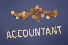 Accountant written with wooden letters on a blue background. To mean a business concept Stock Photo