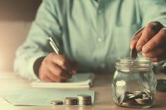 accountin дела с деньгами сбережений при рука кладя монетки внутри стоковое изображение rf