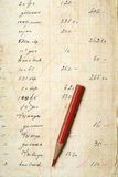 Accounting. A red pencil on yellowed paper with accounting figures Stock Images