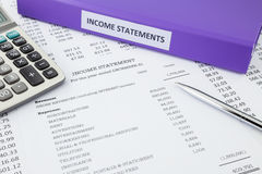 Accounting for business income statement. Document binder and income statement reports with detail list of revenues and expenses, pen pointing at credit revenues Royalty Free Stock Photography