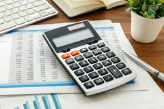 Accounting with calculator and computer keyboard. Financial accounting with calculator and accounting data on wooden table Royalty Free Stock Photography