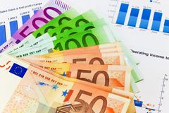Accounting concept. Close view of Euro banknotes on financail reports Stock Photos