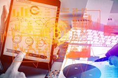 Accounting concept. Businessmen working at office desk with tablet, report and abstract bitcoin interface. Accounting concept. Double exposure Royalty Free Stock Image