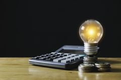 Accounting concept with coins, light bulb and calculator on table.  stock photo