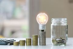 Accounting concept with coins, light bulb and calculator on table.  royalty free stock photo