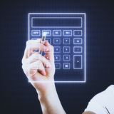 Accounting concept. Male hand using abstract digital calculator on dark background. Accounting concept Stock Photos