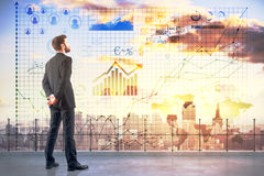Accounting concept. Side view of young man on rooftop looking at city with abstract business charts and diagrams. Accounting concept Stock Images