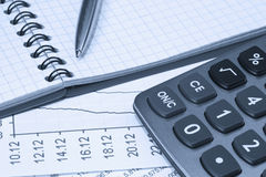 Accounting.dual tone. Calculator, notepad and pen on financial statements Stock Image