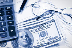 Accounting,dual tone. Calculator, Dollar, glasses and pen on the background of the financial statements Stock Photo