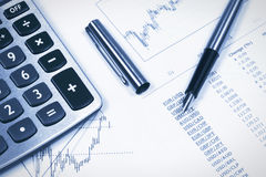 Accounting,dual tone. Calculator,  pen against the backdrop of dollars and the financial statements Stock Images