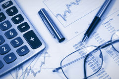 Accounting,dual tone. Calculator,  glasses and pen on the background of the financial statements Royalty Free Stock Image