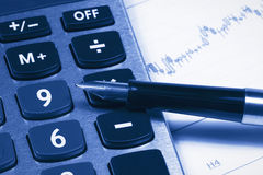 Accounting,dual tone. Calculator,  pen against the backdrop of  the financial statements Royalty Free Stock Photography
