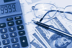 Accounting,dual tone. Calculator, Dollar, glasses and pen on the background of the financial statements Stock Photos