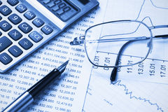 Accounting,dual tone. Calculator,  glasses and pen on the background of the financial statements Stock Photo