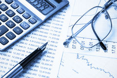 Accounting,dual tone. Calculator,  glasses and pen on the background of the financial statements Stock Photography
