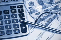 Accounting,dual tone. Calculator, Dollar, glasses and pen on the background of the financial statements Stock Photography