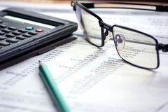 Accounting  files with glasses and mathematical computer. Characteristic accounting paperwork with files and mathematical calculator Royalty Free Stock Photos