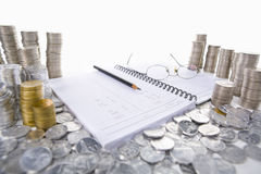 Accounting ledger between piles of coins Stock Photos