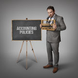 Accounting policies text on blackboard with businessman Stock Images