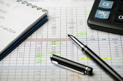 Accounting records in tables, a paper notebook with calculations and a black pen royalty free stock image