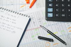 Accounting records in tables, a paper notebook with profit calculations, a pen and a calculator stock image