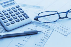 Accounting. Work space with calculator, glasses,pen and profit and loss statements Stock Photos