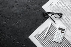 Accounting work space with calculator, profit and tables on dark desk top view mock-up. Accounting work space with calculator, profit and tables on dark desk Royalty Free Stock Image