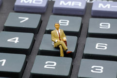 Accountnat. Miniature Accountant Sitting on a Calculator Button