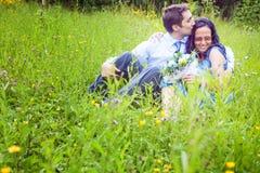 Accouplez avoir un baiser romantique franc dans l'herbe Photographie stock libre de droits