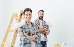 accouplez chaque étreindre à la maison de fixation heureuse neuf l'autre sourire de peinture leur aux outils Photographie stock